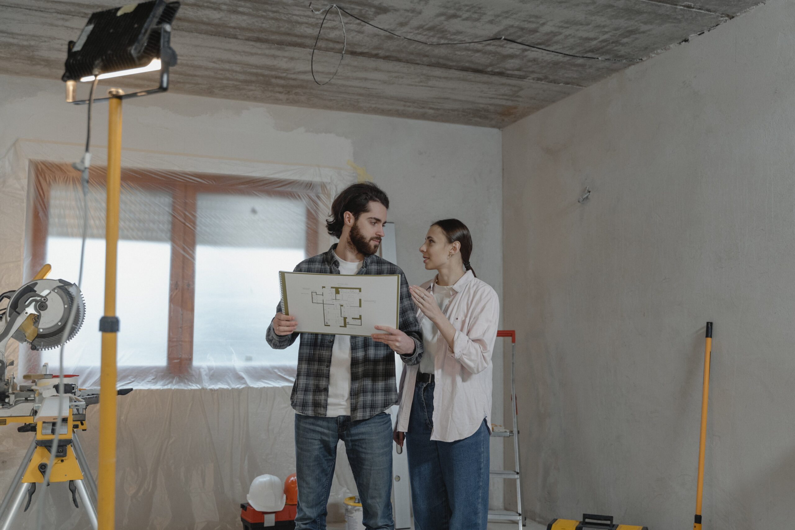 Two people looking at home's blueprints.
